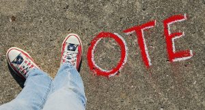 "The word ""VOTE"" with the V spelled with two shoes"